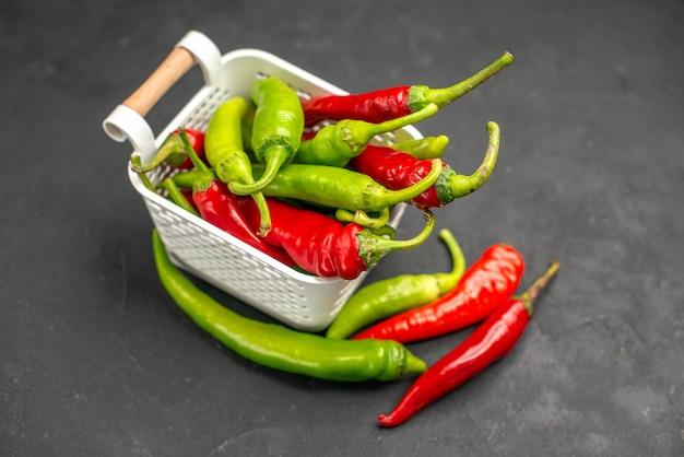 Vorderansicht farbige würzige paprika im korb auf dunklem hintergrund essen farbe foto salat gesundheit