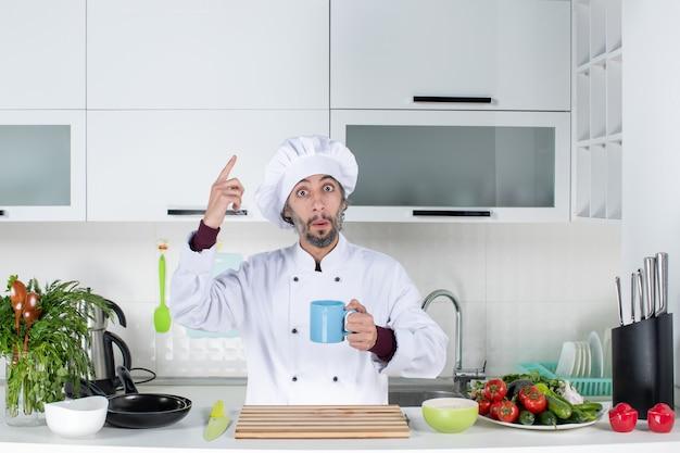 Vorderansicht fragte sich männlicher koch in kochmütze, der eine tasse hinter dem küchentisch hochhält?
