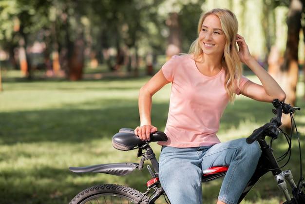 Vorderansicht frau, die auf fahrrad ruht und wegschaut