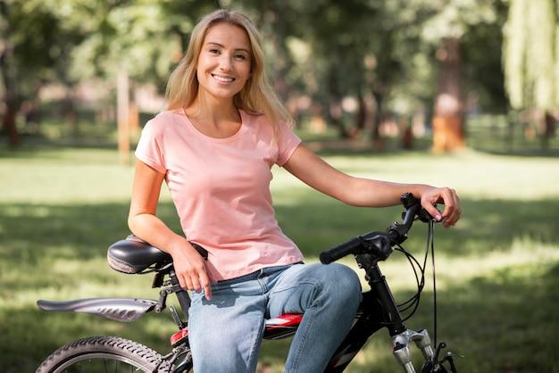Vorderansicht frau, die auf fahrrad ruht