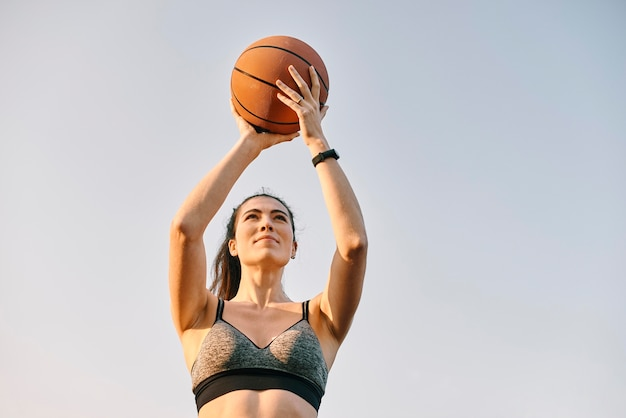 Vorderansicht frau, die basketball allein spielt