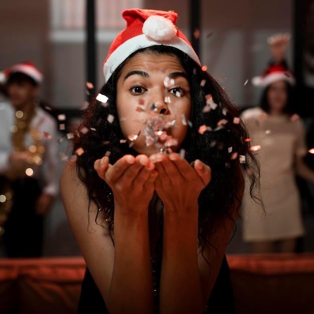 Vorderansicht frau, die den weihnachtsmann trägt, der einige konfetti bläst