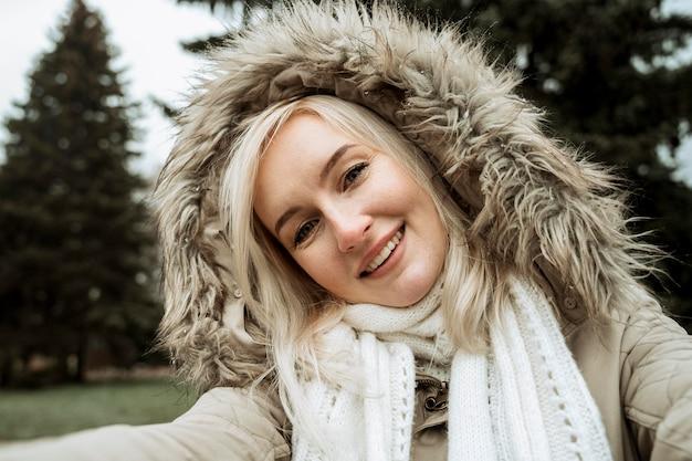 Vorderansicht frau, die ein selbstfoto im winter macht