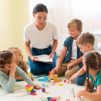 Vorderansicht frau, die kinder im kindergarten unterrichtet