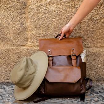 Vorderansicht frau, die rucksack vom boden packt