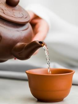 Vorderansicht frau, die tee aus tontekanne gießt