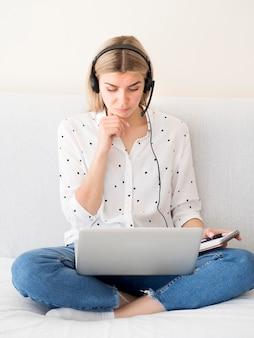 Vorderansicht frau, die vom laptop-e-learning-konzept liest