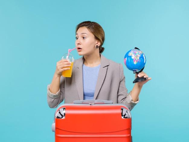 Vorderansicht frau im urlaub, die frischen saft und globus auf hellblauer schreibtisch-seereise-urlaubsreise hält