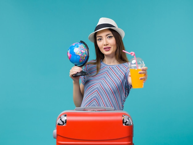 Vorderansicht frau im urlaub hält saft und globus auf dem blauen hintergrund seereise urlaub sommerreise reise