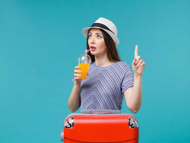 Vorderansicht frau im urlaub mit ihrer roten tasche, die ihren saft auf hellblauem hintergrundreise-sommerseereise-reiseurlaub hält