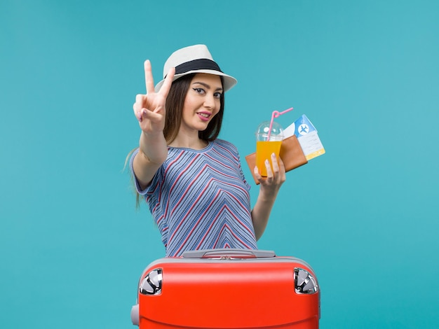 Vorderansicht frau im urlaub mit ihrer roten tasche, die tickets und saft auf hellblauem hintergrundreise-reise-reise-urlaubsfrau hält