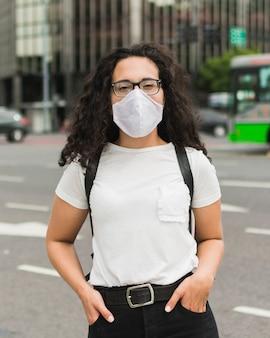 Vorderansicht frau mit der medizinischen maske, die aufwirft