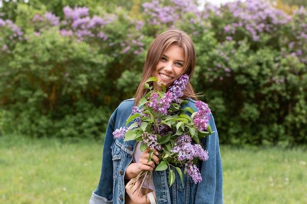 Vorderansicht frau mit lila blumenstrauß
