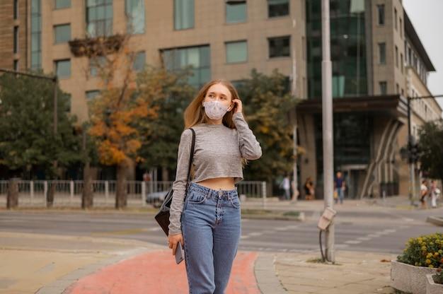 Vorderansicht frau mit medizinischer maske außerhalb