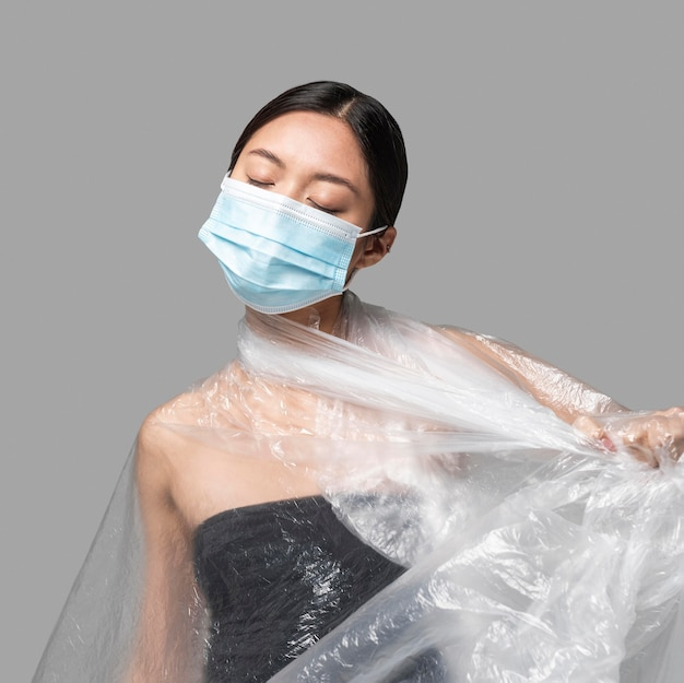 Vorderansicht frau mit medizinischer maske, die ihren körper in plastik bedeckt hat