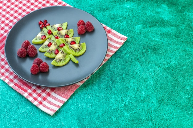 Vorderansicht frisch geschnittene kiwis mit himbeeren auf grüner oberfläche beere exotische fruchtfoto tropische farbe