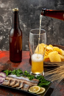 Vorderansicht frisch geschnittener fisch mit grüns und bier auf der dunklen foto-snack-fleischmahlzeit-meeresfrüchte-farbe