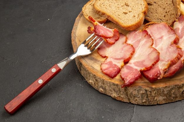 Vorderansicht frisch geschnittener schinken mit brotscheiben auf dunklem snack-mahlzeit-farblebensmittel-fleischschwein