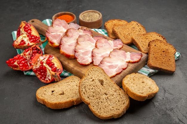 Vorderansicht frisch geschnittener schinken mit gewürzen brot und granatäpfel auf dunkler mahlzeit farbe lebensmittel rohes foto fleisch