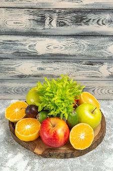 Vorderansicht frische äpfel mit geschnittenen orangen auf grauem hintergrund reife reife früchte frischer apfel