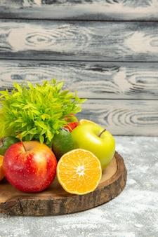 Vorderansicht frische äpfel mit in scheiben geschnittenen orangen auf dem grauen hintergrund reife reife früchte frischer apfel
