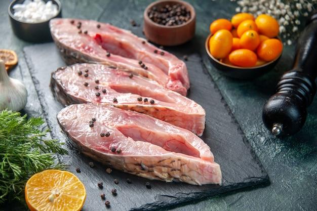 Vorderansicht frische fischscheiben mit pfeffer auf einer dunklen oberfläche fleisch rohe mahlzeit wasser foto ozean meeresfrüchte farbe abendessen