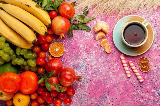 Vorderansicht frische fruchtzusammensetzung mit tasse tee auf der hellrosa oberfläche