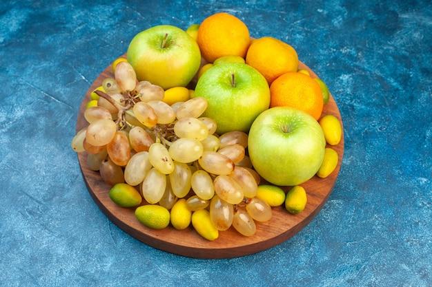 Vorderansicht frische früchte äpfel mandarinen und trauben auf blauem saft obst mellow fotofarbe gesunde lebenszusammensetzung