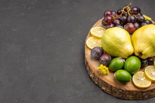 Vorderansicht frische früchte trauben zitronenscheiben pflaumen und quitten auf dem dunklen hintergrund frische früchte reife baumpflanze