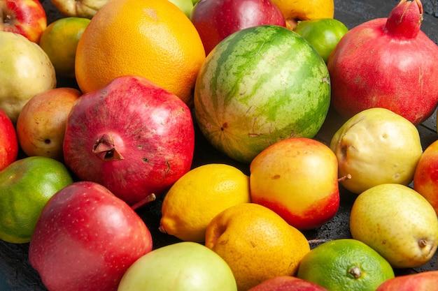 Vorderansicht frische früchte zusammensetzung äpfel birnen und mandarinen auf dunkelblauem schreibtisch obst reife baumfarbe frisch ausgereift viele