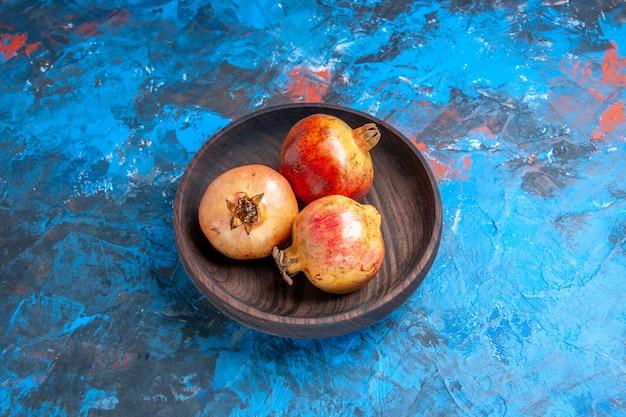 Vorderansicht frische granatäpfel in holzschale auf blau