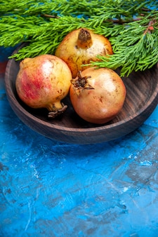 Vorderansicht frische granatäpfel in holzschale kiefernzweig auf blauem hintergrund mit kopierraum