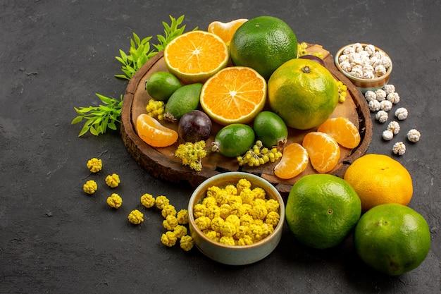 Vorderansicht frische grüne mandarinen mit feijoas und bonbons auf dem dunklen raum