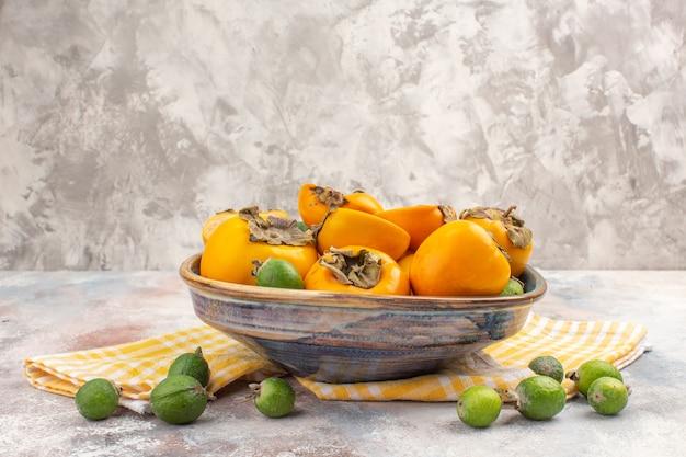 Vorderansicht frische kaki in einer schüssel gelbes küchentuch feykhoas auf nacktem hintergrund mit freiem platz