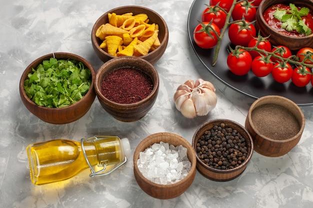 Vorderansicht frische kirschtomaten innerhalb platte mit verschiedenen gewürzen auf weißer oberfläche gemüsemehl lebensmittelsalat