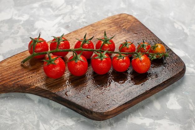 Vorderansicht frische kirschtomaten reifes ganzes gemüse auf hellweißem oberflächengemüsemehl-nahrungsmittelsalat