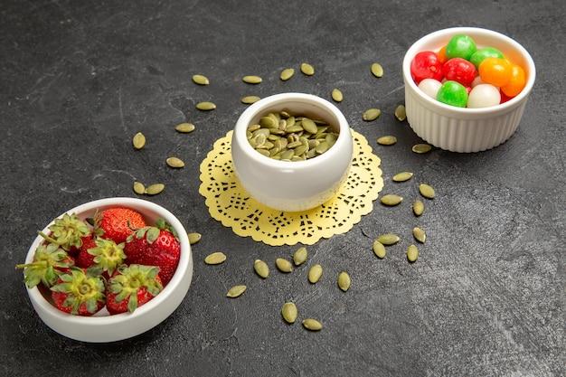 Vorderansicht frische kürbiskerne mit süßigkeiten und erdbeeren auf grauem hintergrund samenfarbe regenbogen-süßigkeitsfrucht