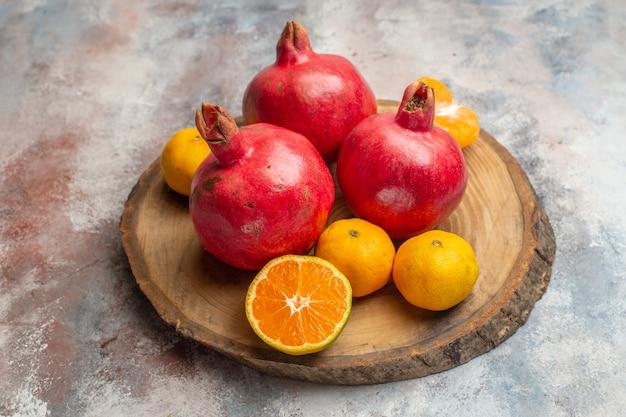 Vorderansicht frische mandarinen mit roten granatäpfeln auf hellem hintergrund foto exotischer saft vitamin geschmack obstbaum farbe
