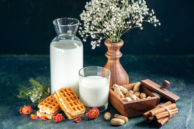 Vorderansicht frische milch mit süßen kleinen kuchen auf dunkelblauem dessert honigkuchen frühstück süßer milchmorgen