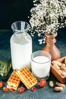 Vorderansicht frische milch mit süßen kleinen kuchen und nüssen auf einem dunkelblauen dessert honigkuchen frühstück süßer kuchen milchmorgen