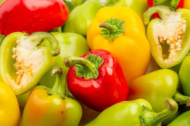 Vorderansicht frische paprika im rahmen auf weißem gemüsepfefferfarbe reife mehlpflanze fotosalat