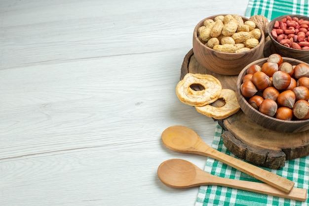 Vorderansicht frische rohe haselnüsse mit erdnüssen auf weißer oberfläche
