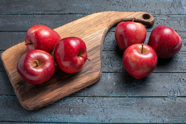 Vorderansicht frische rote äpfel milde reife früchte auf dunkelblauem schreibtisch früchte farbe rotes pflanzenvitamin frisch vitamin