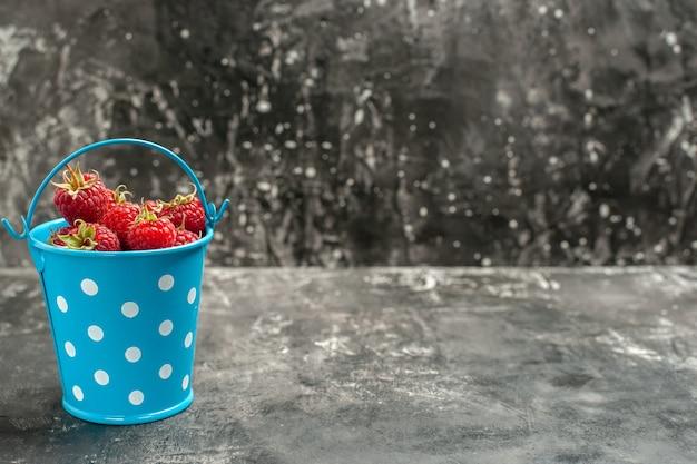 Vorderansicht frische rote himbeeren in einem kleinen korb auf grauer fruchtfarbe preiselbeere wilde fotobeere freier platz für text
