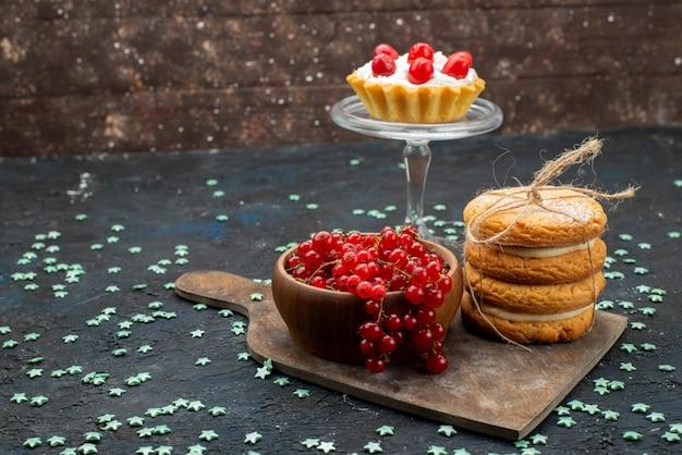 Vorderansicht frische rote preiselbeeren in schüssel mit sahnefüllung sandwichplätzchen auf der dunklen oberfläche kuchen zucker süß