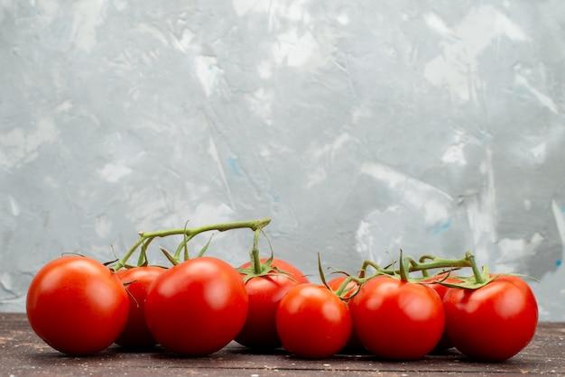 Vorderansicht frische rote tomaten reif und ganz auf holz, braune gemüsefrucht beeren lebensmittelfarbe
