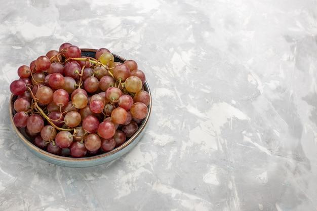 Vorderansicht frische rote trauben saftig milde süße früchte auf dem hellweißen schreibtisch obst frischen milden saft wein