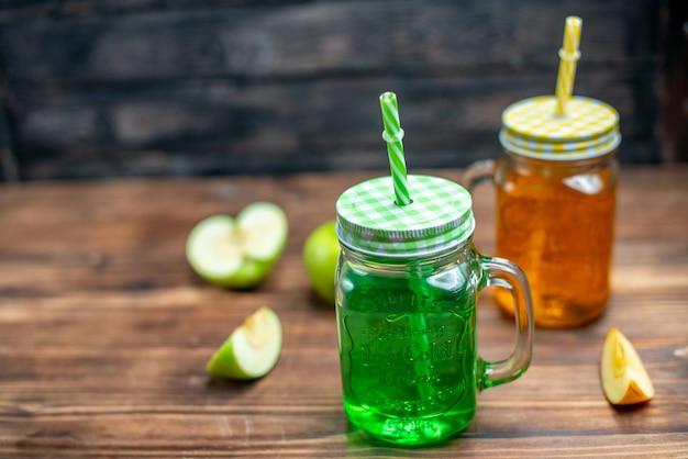 Vorderansicht frische säfte in glasdosen mit früchten auf dunkler farbe trinken cocktailfrucht