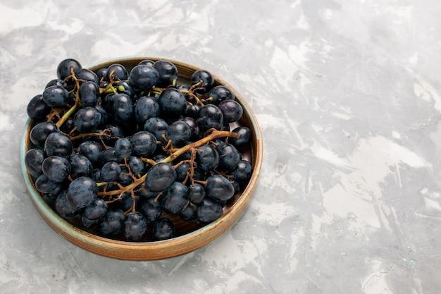 Vorderansicht frische schwarze trauben saftig milde süße früchte auf dem hellweißen schreibtisch früchte frischen milden saft wein