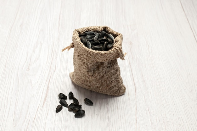 Vorderansicht frische sonnenblumenkerne schwarz gefärbte samen in kleiner tasche auf weißem hintergrund samen-snack-foto viele öle